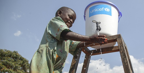 "On 13 August 2018, Jean Marie Bofio, UNICEF's WASH Officer, talks with a girl as she washes her hands in order to prevent the spread of Ebola near Mangina, North Kivu, the Democratic Republic of the Congo (DRC). ""Children and women are among the first victims of the Ebola outbreak in the country. But there is hope and everything is done to stop Ebola. Water and sanitation are critical in this fight because hygiene is the best way to prevent the spread of the this deadly disease,"" says Jean Marie Bofio."