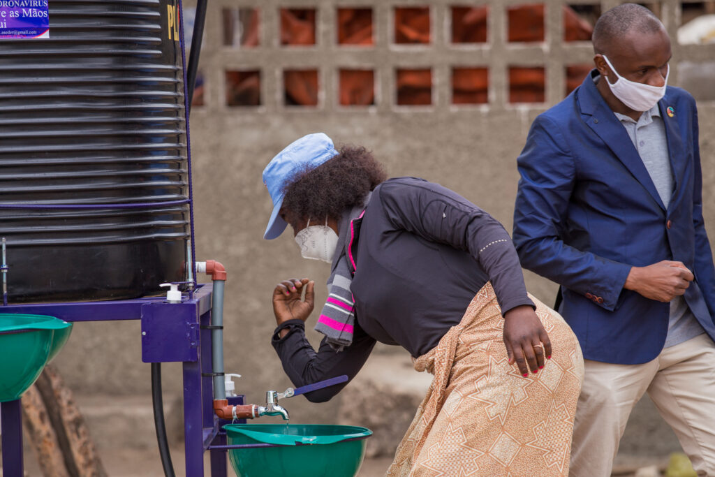 Market vendor Mariana Langa washes her hands at a public hand washing station.