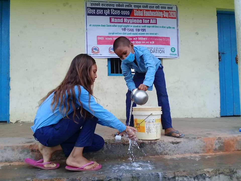 A child assisting to wash hands to his senior