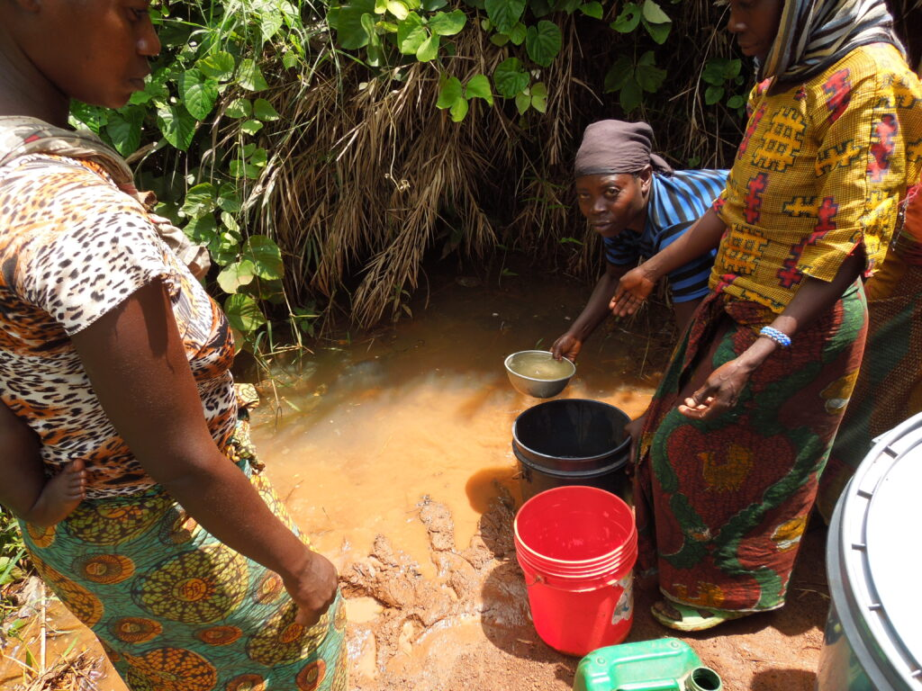 Women collecting water from Mazungwe Spring in Western Tanzania
