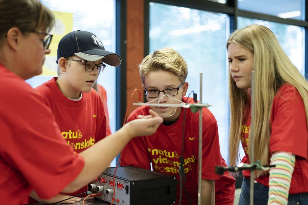 Børn iført Naturvidensabsfestival T-shirts laver fysikforsøg