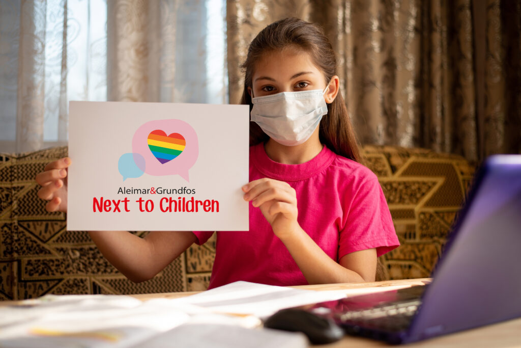 Girl with facemask holding Next to children sign